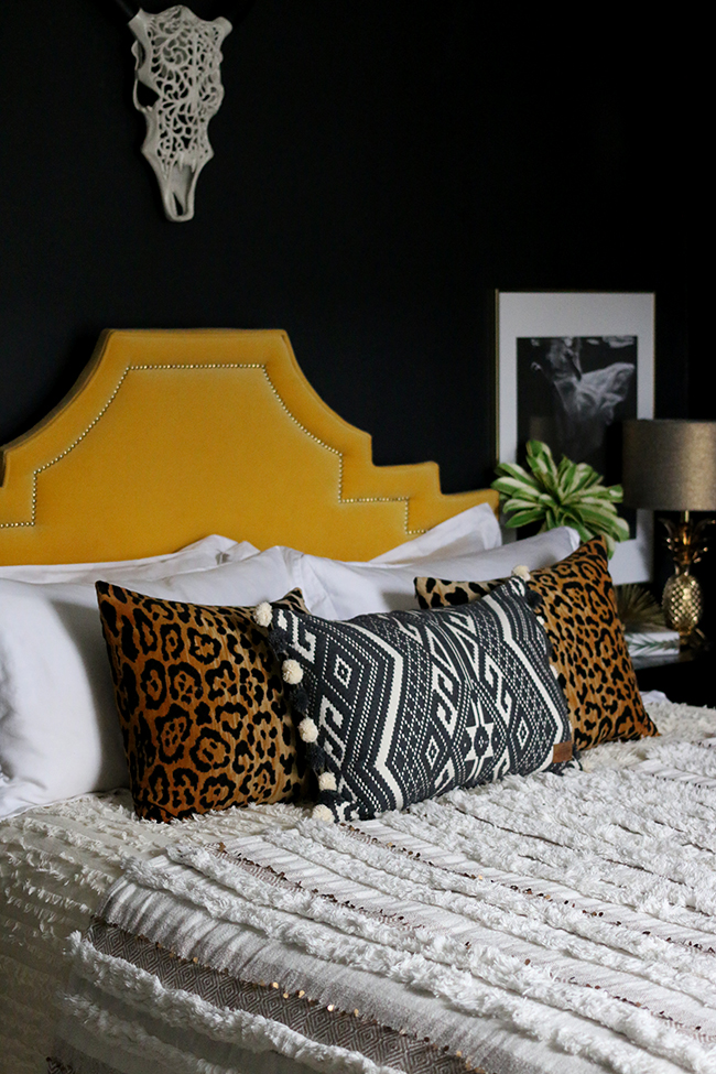 black bedroom with yellow velvet headboard and leopard print cushions