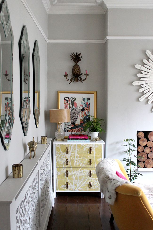 white wallpapered chest of drawers with gold accessories