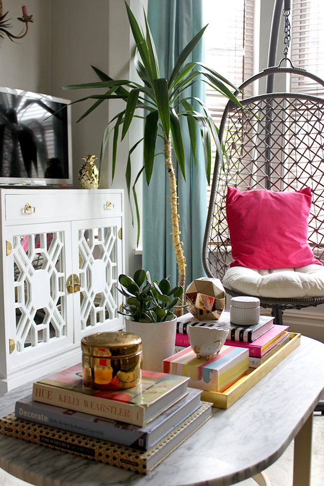 coffee table vignette with hanging chair in background and vintage tv cabinet