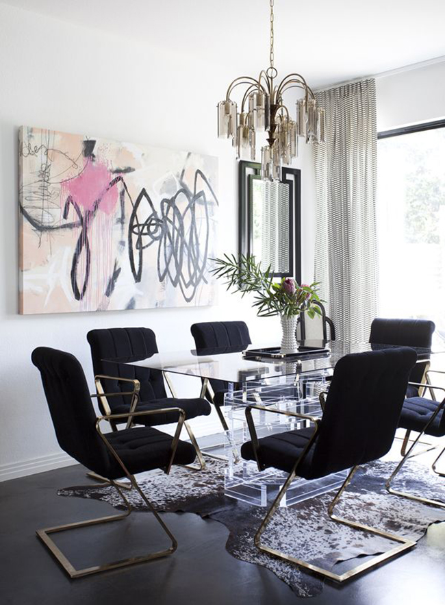 white dining room with black chairs and abstract art