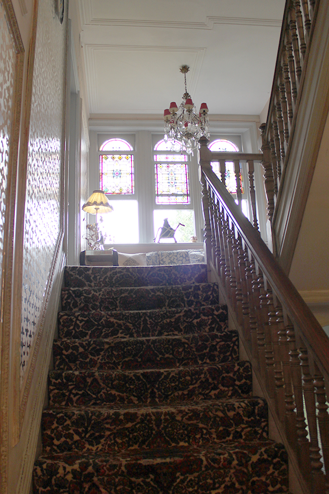 stairwell with patterned carpet and stained glass Swoon Worthy - LivingEtc House Tour