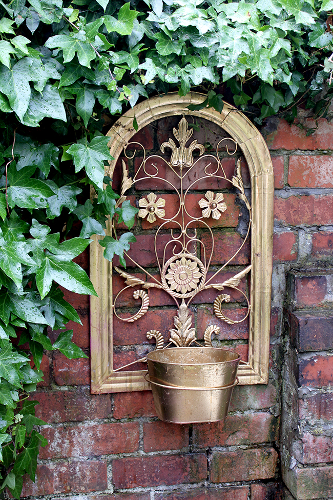 Swoon Worthy - gold planter and brick garden wall