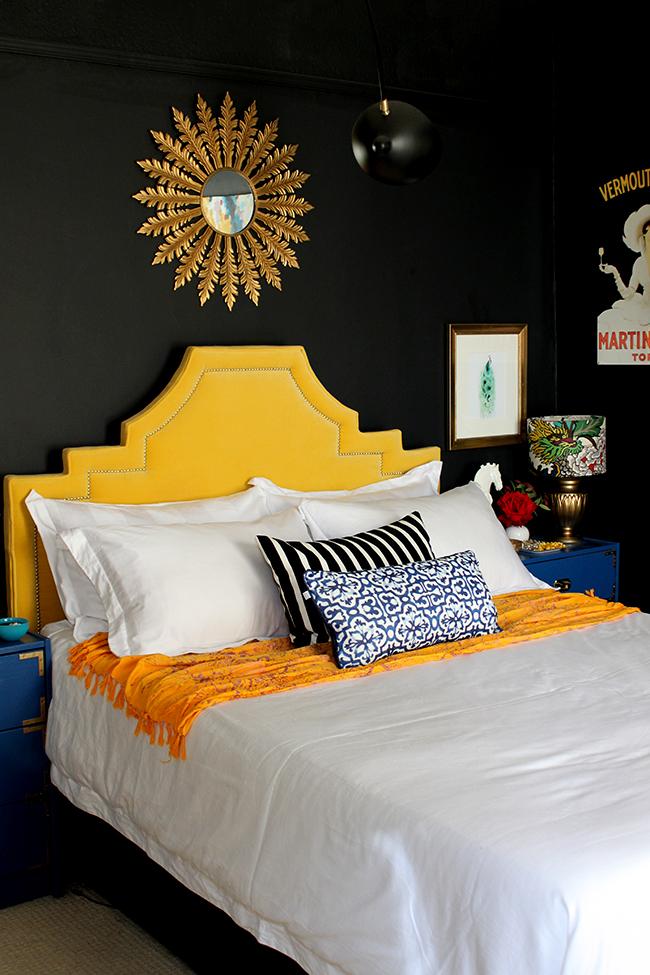 Swoon Worthy black bedroom with yellow velvet headboard