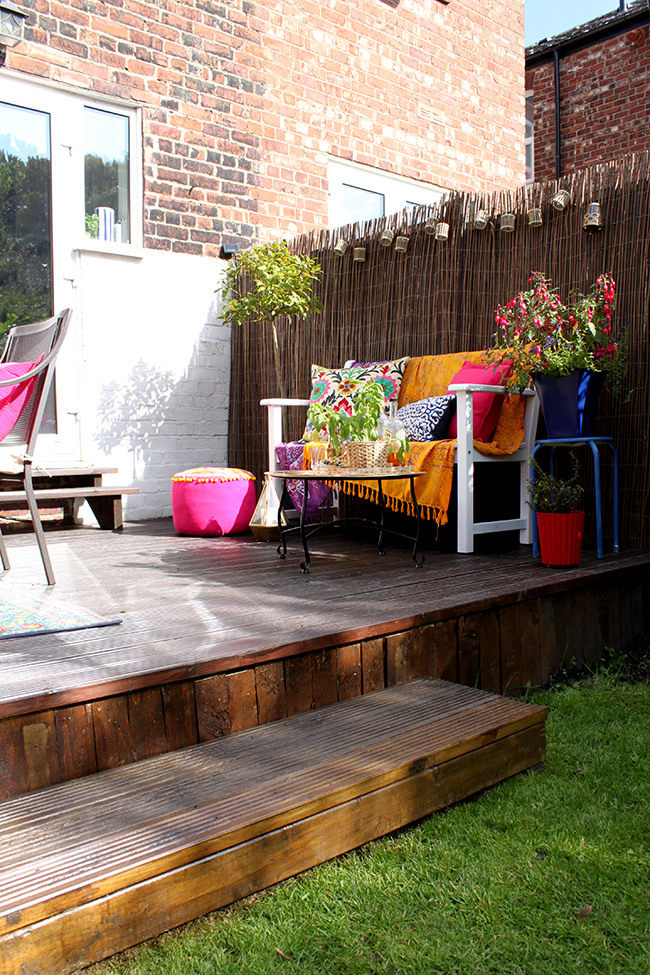 eclectic boho glam garden reveal swoon worthy boho textiles on white bench
