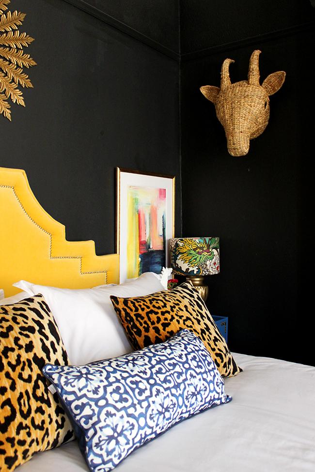 Swoon Worthy bedroom - yellow headboard, abstract art, leopard cushions, black walls