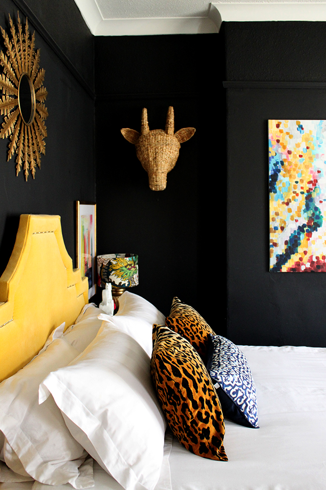 Swoon Worthy bedroom - yellow headboard, abstract art, leopard cushions, black walls