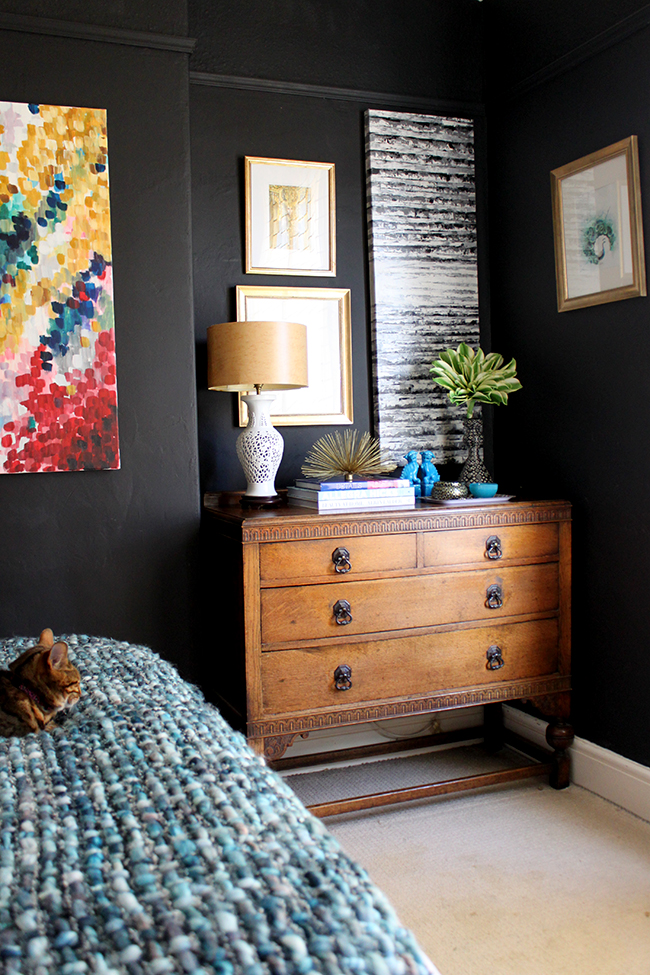 Swoon Worthy bedroom - vintage chest of drawers, black walls, colourful art