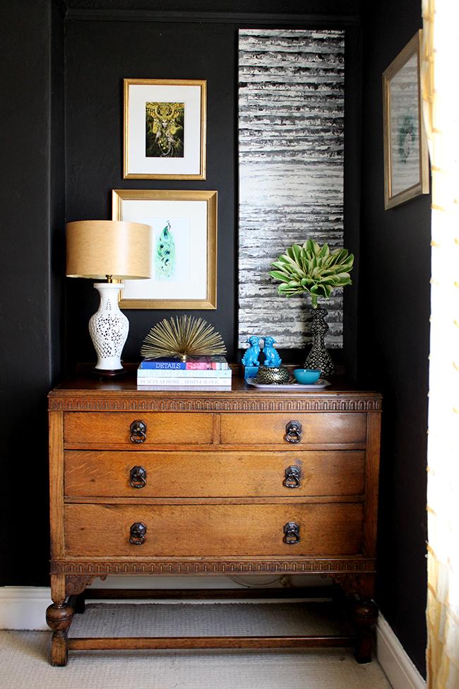 Swoon Worthy bedroom - vintage dresser, black walls, colourful art