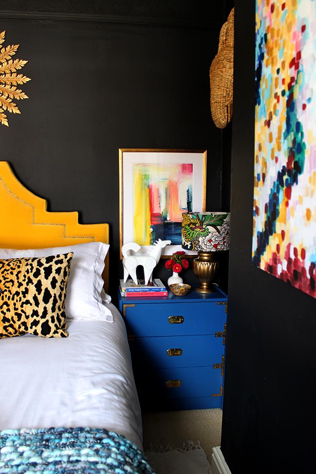 Swoon Worthy bedroom - blue ikea rast hacks, colourful abstract art, yellow headboard, black walls