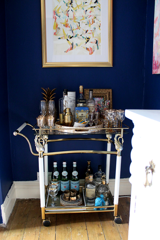 Swoon Worthy dining room - dark blue wall, vintage brass bar cart