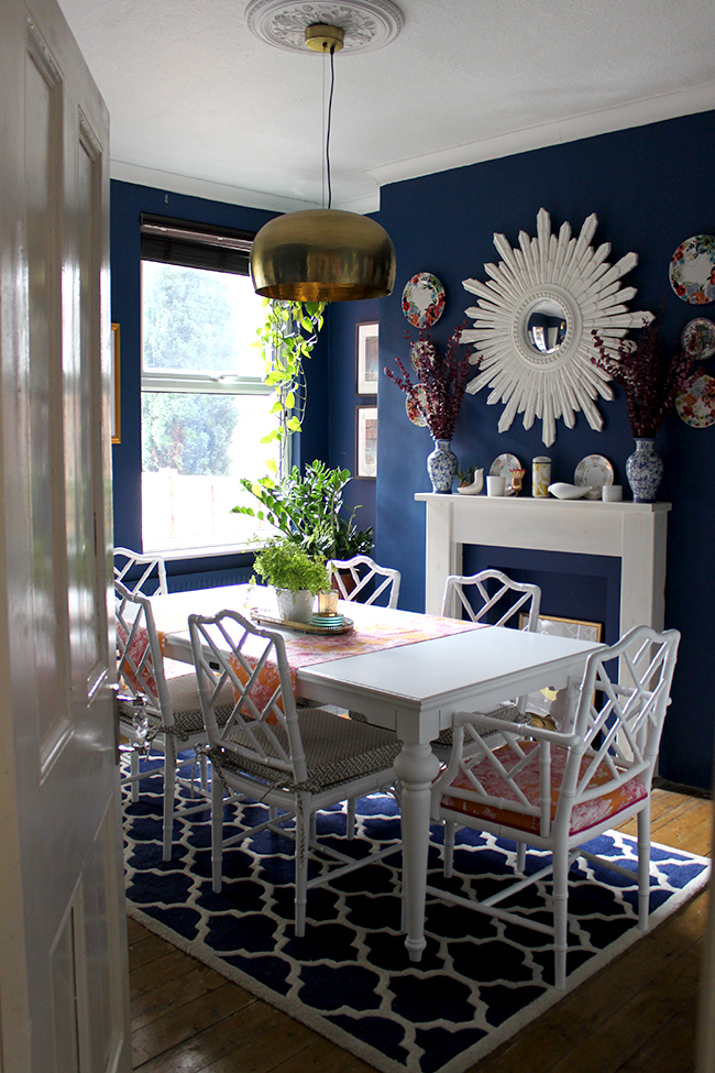 Swoon Worthy dining room - white faux bamboo chairs with dark blue walls