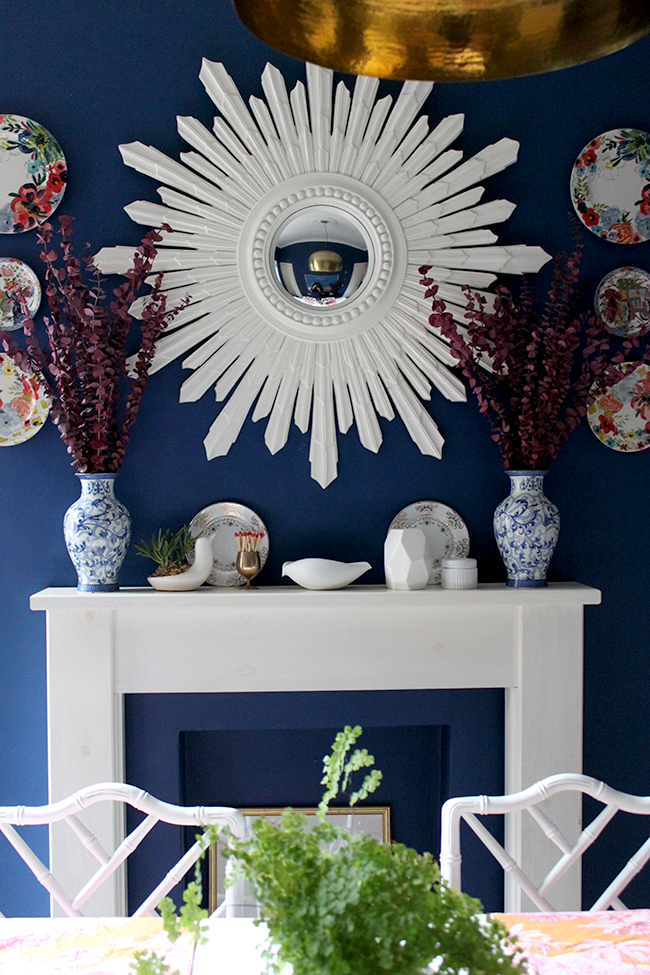 Swoon Worthy dining room - white mantle blue walls white starburst mirror and cranberry red eucalyptus