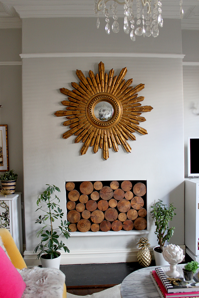 Swoon Worthy living room - gold star burst mirror, grey walls, decorative logs in fireplace