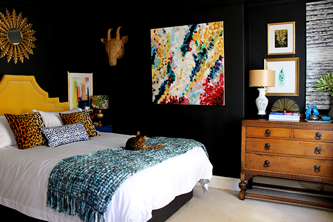 Swoon Worthy bedroom - black walls with yellow headboard, vintage dresser and colourful art