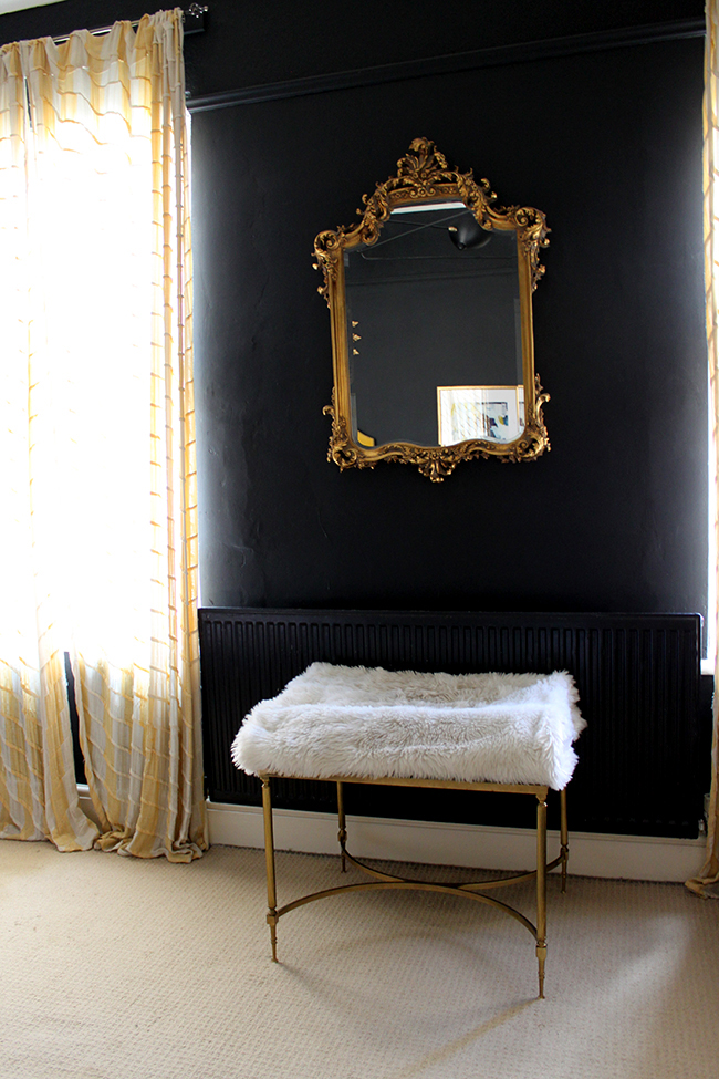 Swoon Worthy - vintage table with faux fur throw cat bed with ornate mirror on black wall
