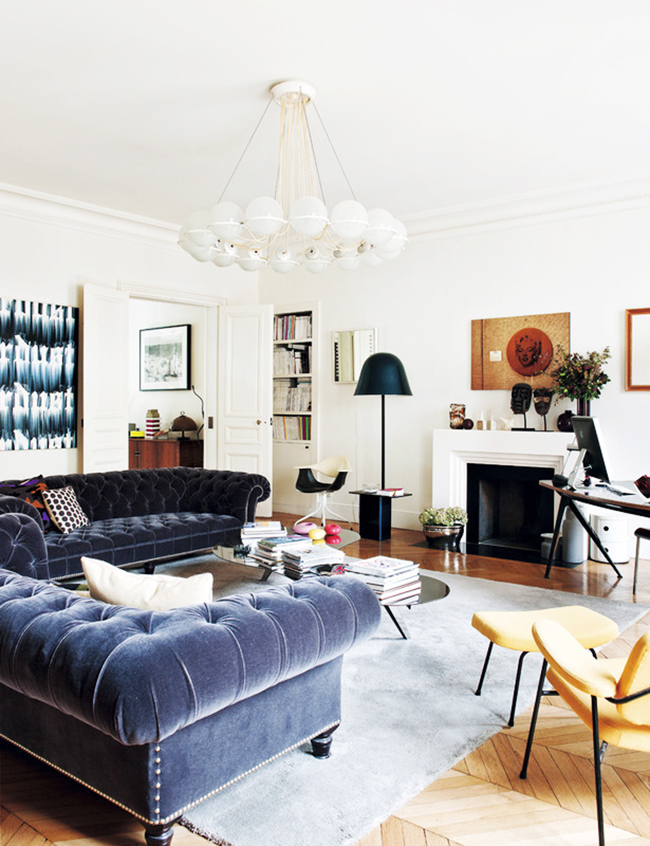 eclectic parisian room with tufted sofas