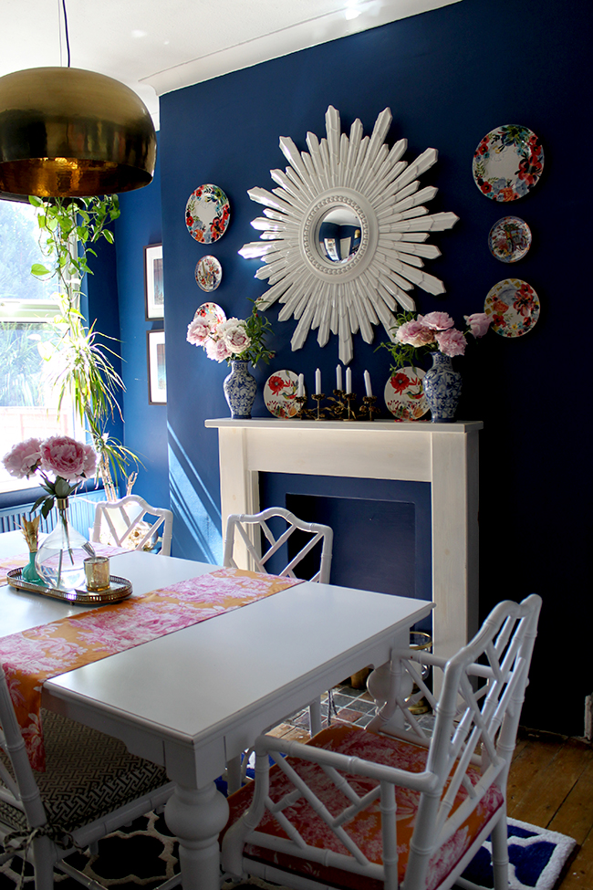 Swoon Worthy dark blue dining room with white furniture and starburst mirror