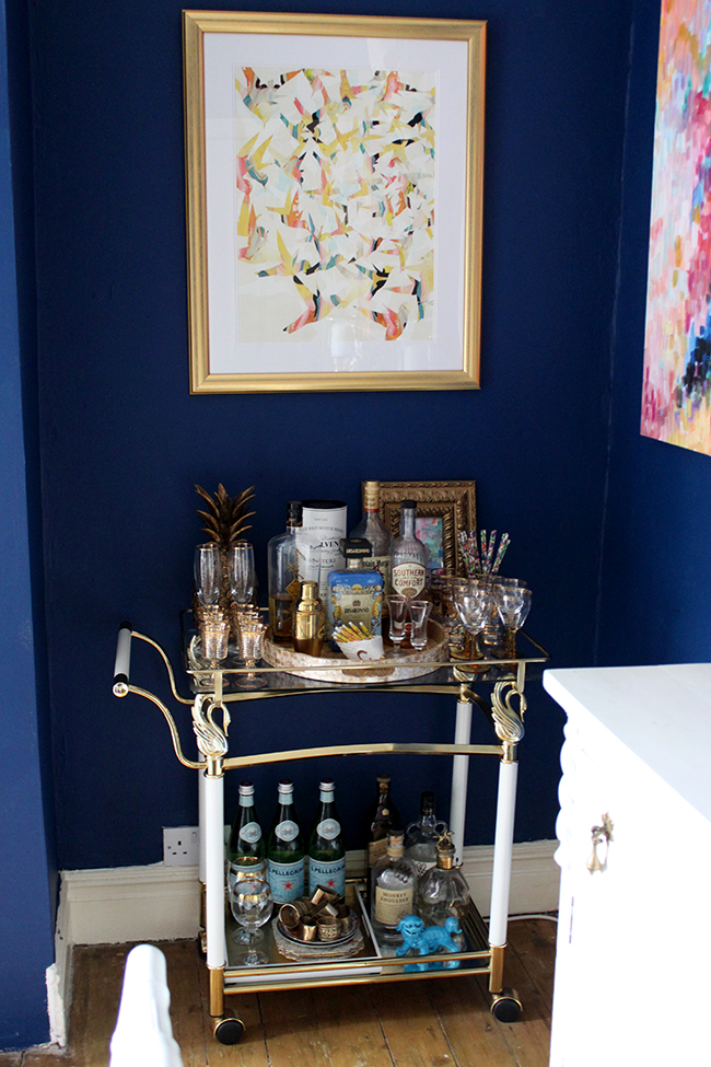 brass barcart against dark blue wall - see more at www.swoonworthy.co.uk