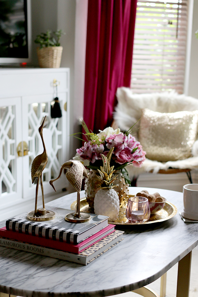 coffee table styling - brass cranes, marble coffee table, pink flowers, white and gold pineapple, brass tray, pink candle