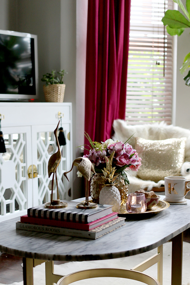 coffee table styling - brass cranes, marble coffee table, pink flowers, white and gold pineapple, brass tray, pink candle - see more on www.swoonworthy.co.uk
