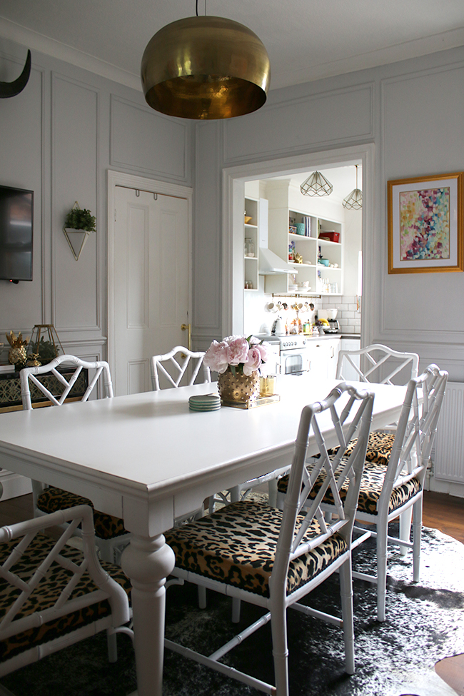 grey dining room with panels and leopard print chairs
