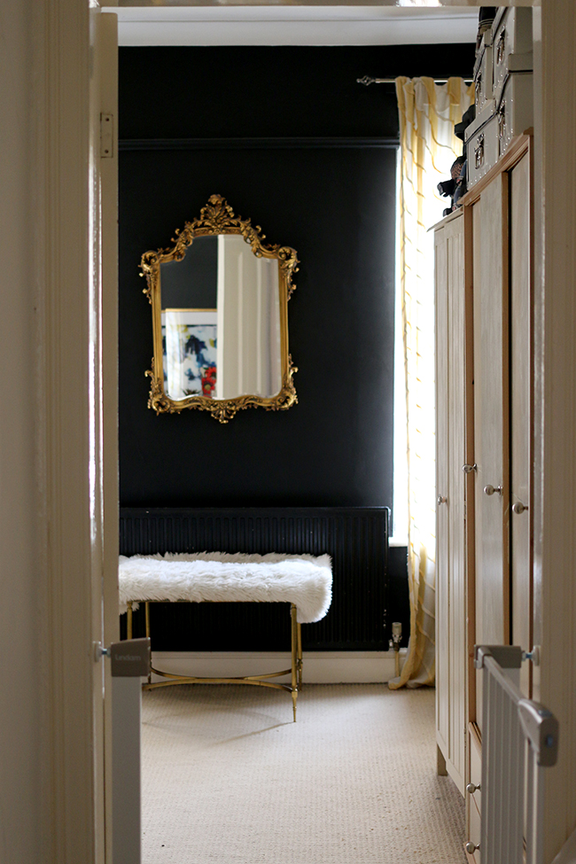 door into black bedroom with gold mirror