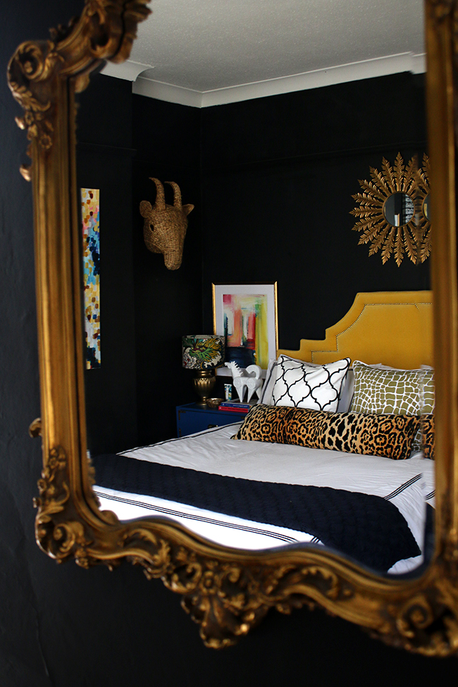 black bedroom with colourful accents, yellow headboard, sunburst mirror - see more on www.swoonworthy.co.uk