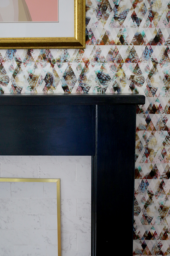 marble tile fireplace with brass trim and black hearth with graphic wallpaper