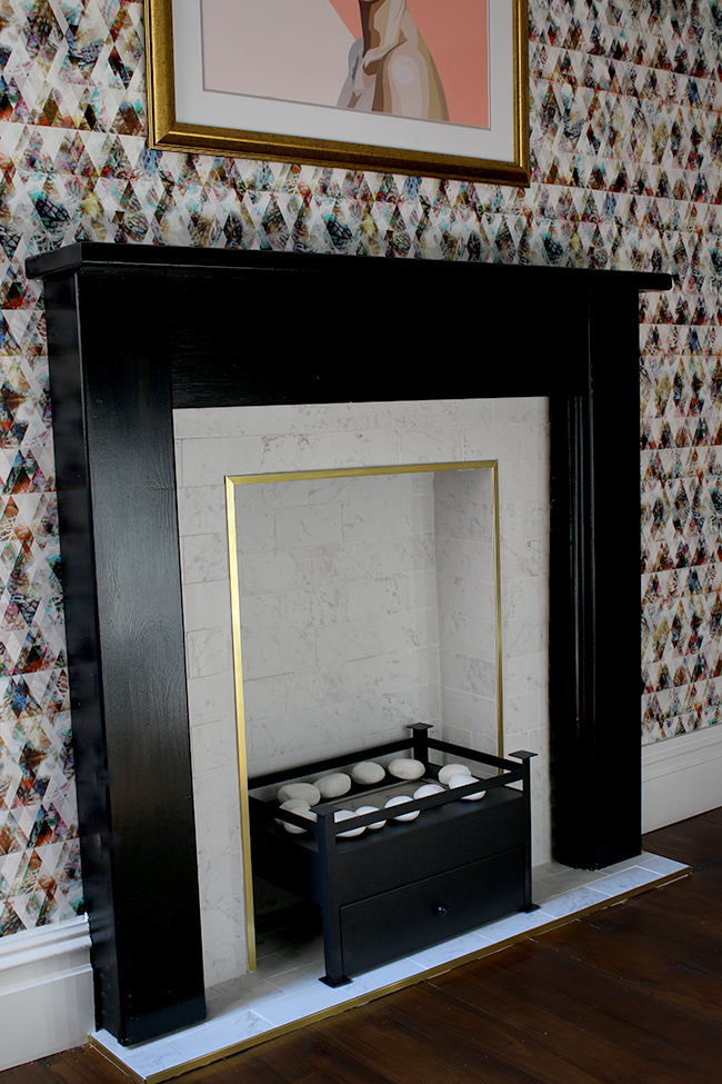 marble tile fireplace with brass trim and black hearth with graphic wallpaper - see the whole process on www.swoonworthy.co.uk