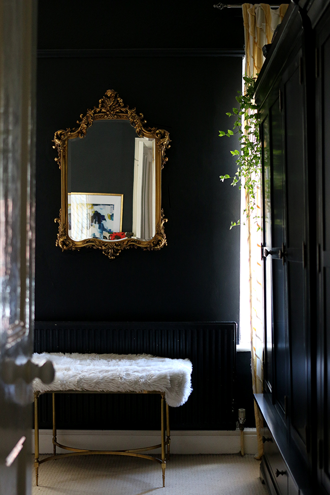 black bedroom with gold ornate mirror and black wardrobes - see more on www.swoonworthy.co.uk