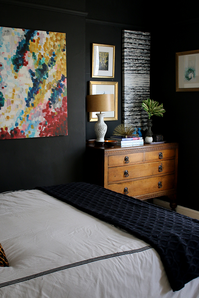 black bedroom with vintage dresser and bright colourful art - see more on www.swoonworthy.co.uk