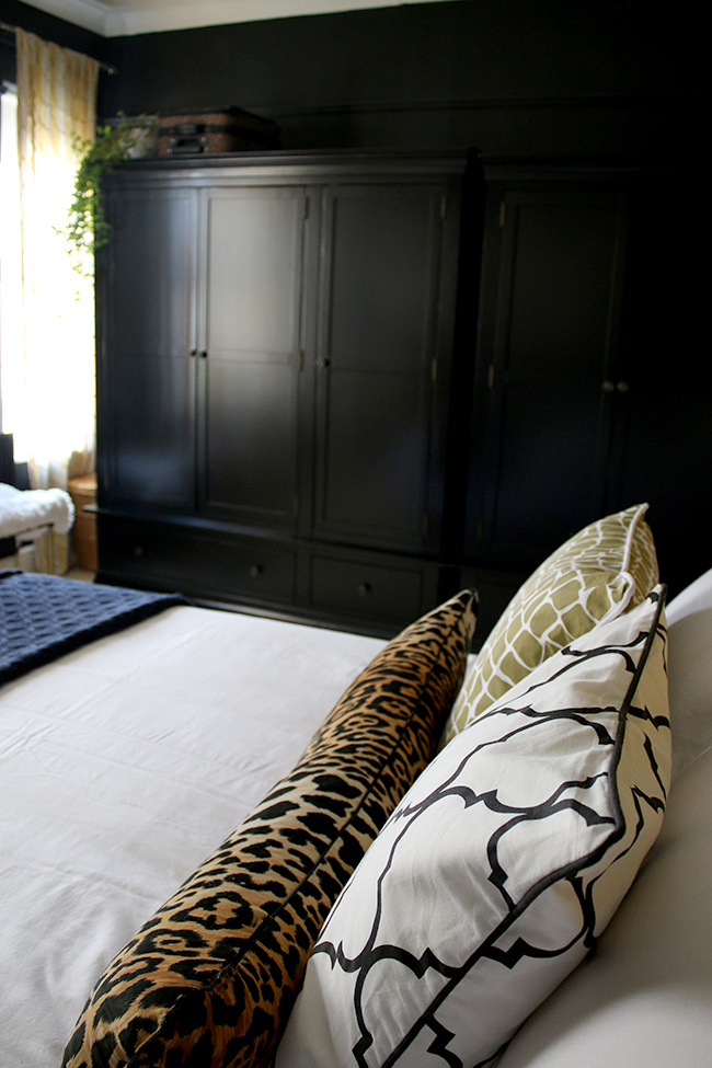 black wardrobes in black bedroom with colourful accents - see more on www.swoonworthy.co.uk