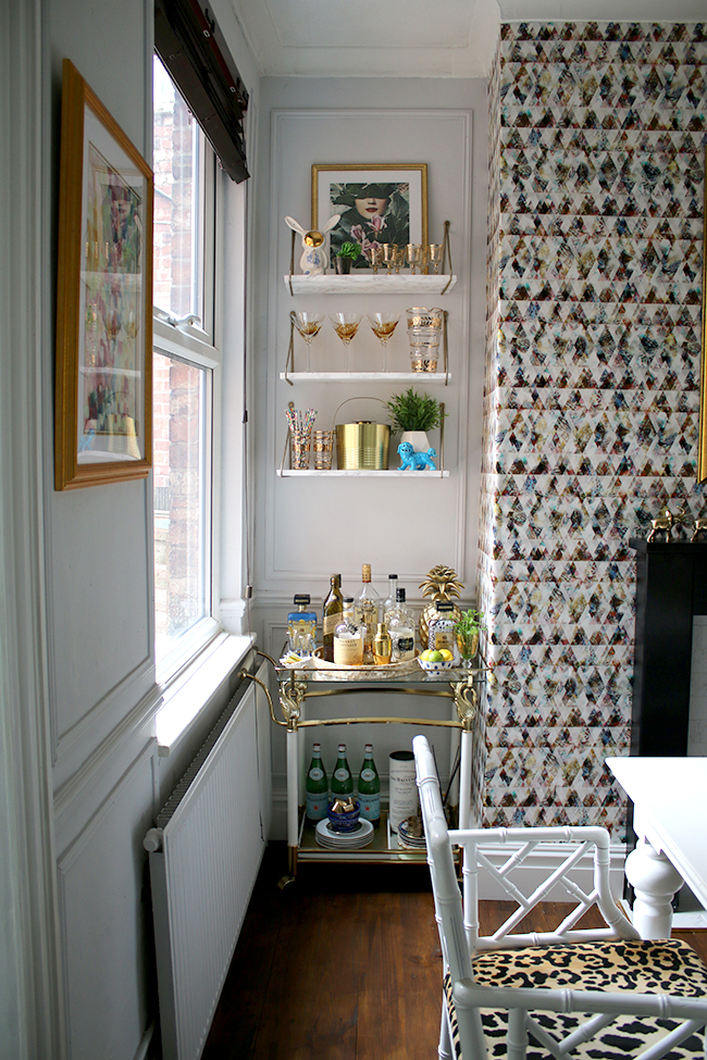 bar cart with marble effect shelves and graphic wallpaper - see more on www.swoonworthy.co.uk