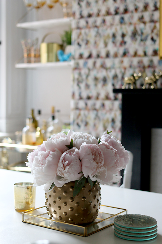 vase of peonies in dining room with graphic wallpaper, black fireplace mantle, gold accents - see more on www.swoonworthy.co.uk