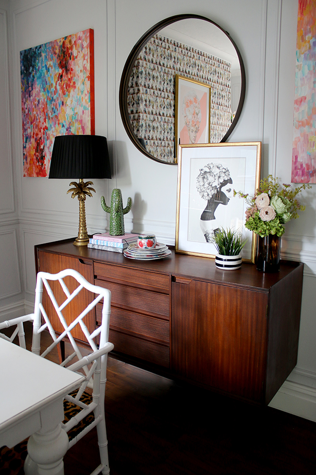 mid-century sideboard with palm tree lamp, round mirror and abstract art - see more on www.swoonworthy.co.uk