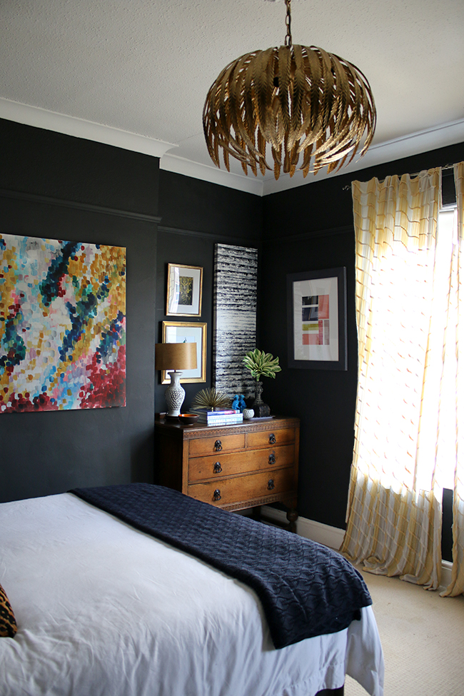 black bedroom with vintage dresser and gallery wall, yellow curtains - see more on www.swoonworthy.co.uk