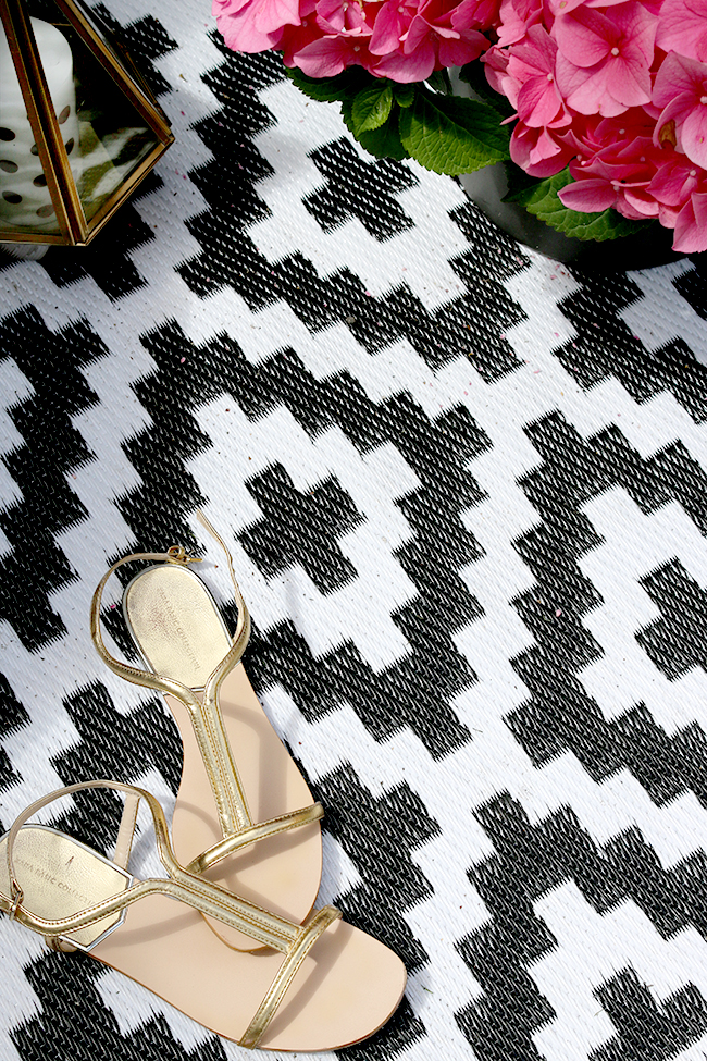 black and white graphic outdoor rug with gold sandles and pink hydrangea