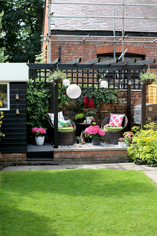 black shed and pergola patio area with hanging lanterns in pink and green