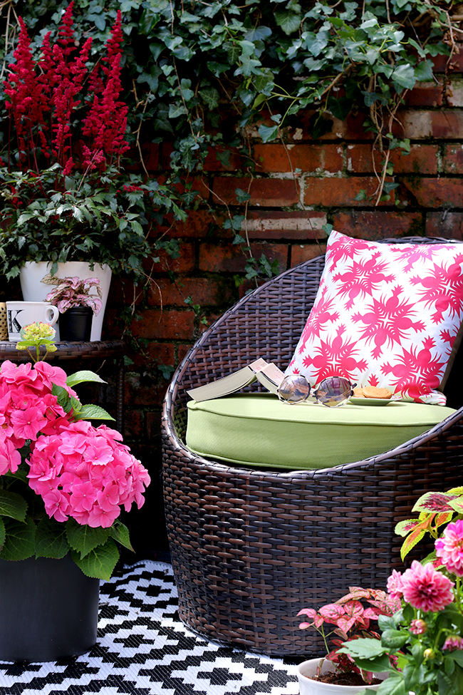 Patio with brick wall with pops of pink and green
