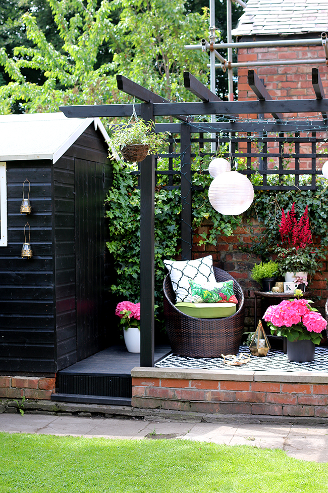 English garden with black pergola and decking area in pink and green