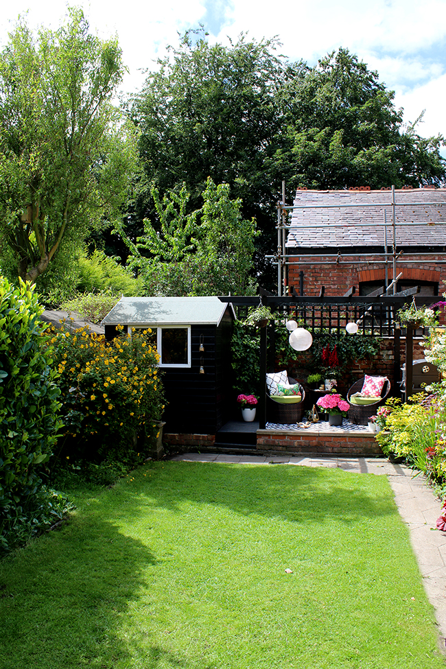 English garden with black pergola and mature plants