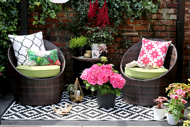 Black Patio with brick wall and black and white outdoor rug, green and pink accessories