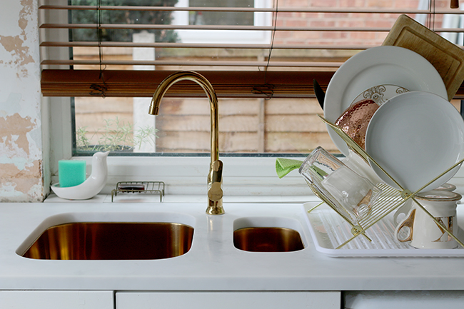 gold undermount sinks and tap with white cararra acrylic worktops