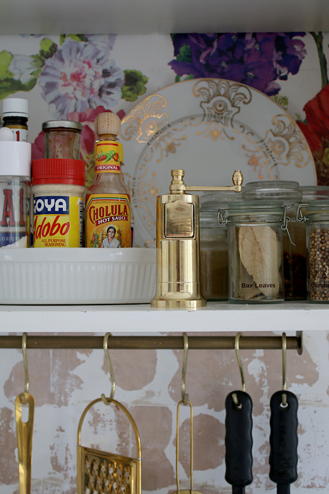 open shelving with gold pepper grinder