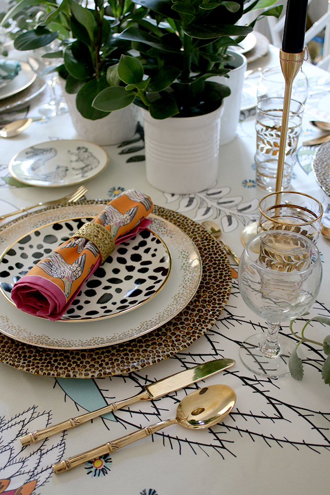 Colourful boho glam table setting with plants and animal prints