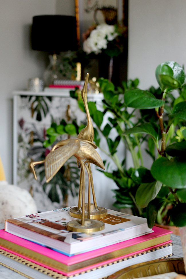 coffee table vignette with brass cranes and houseplants