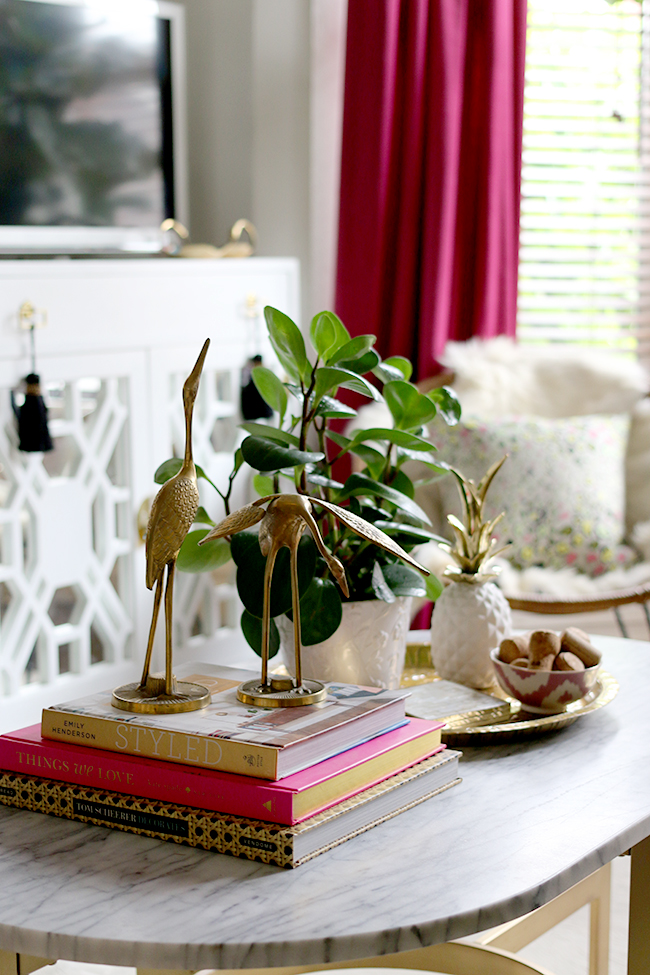 marble coffee table styling vignette with brass cranes