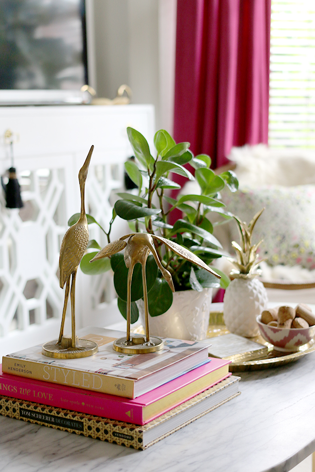 eclectic boho glam coffee table vignette with brass cranes
