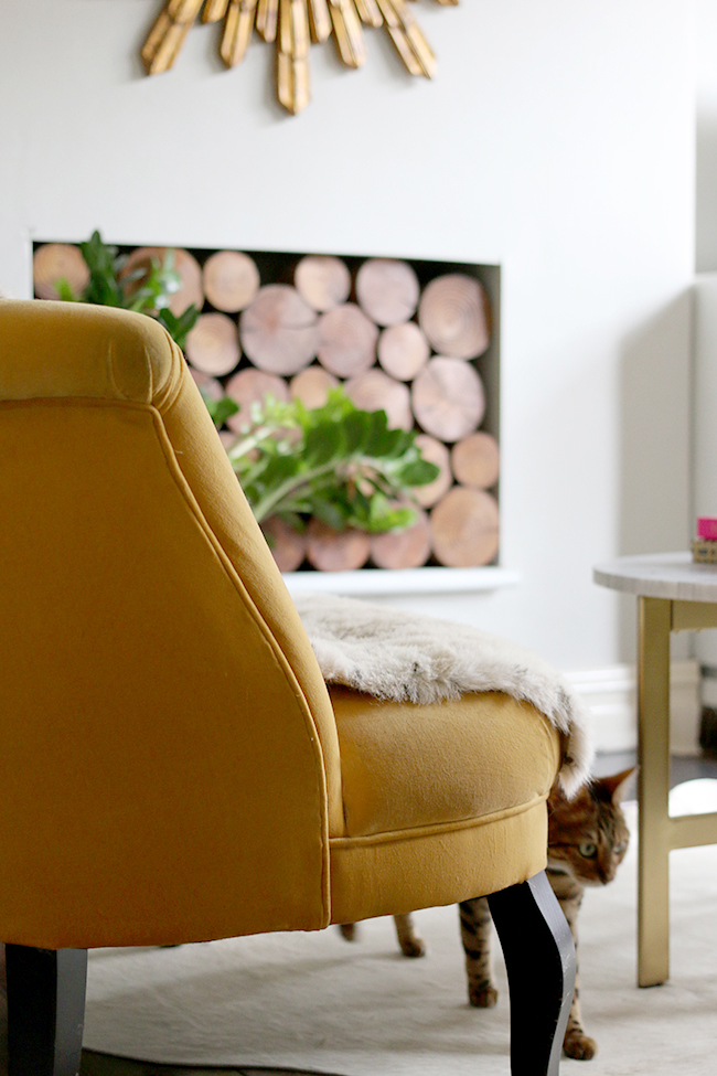 yellow sofa in living room with decorative logs in fireplace