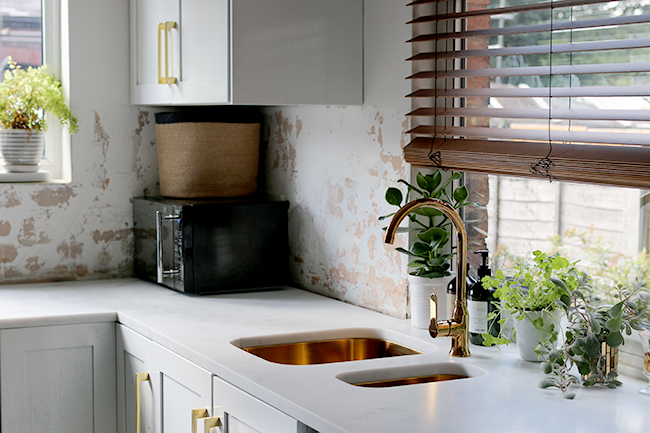 kitchen-with-gold-tap-and-sink-with-marble-worktops